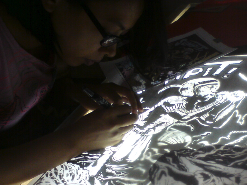 Examining details over the lightbox for one of JP Cuison's posters.
